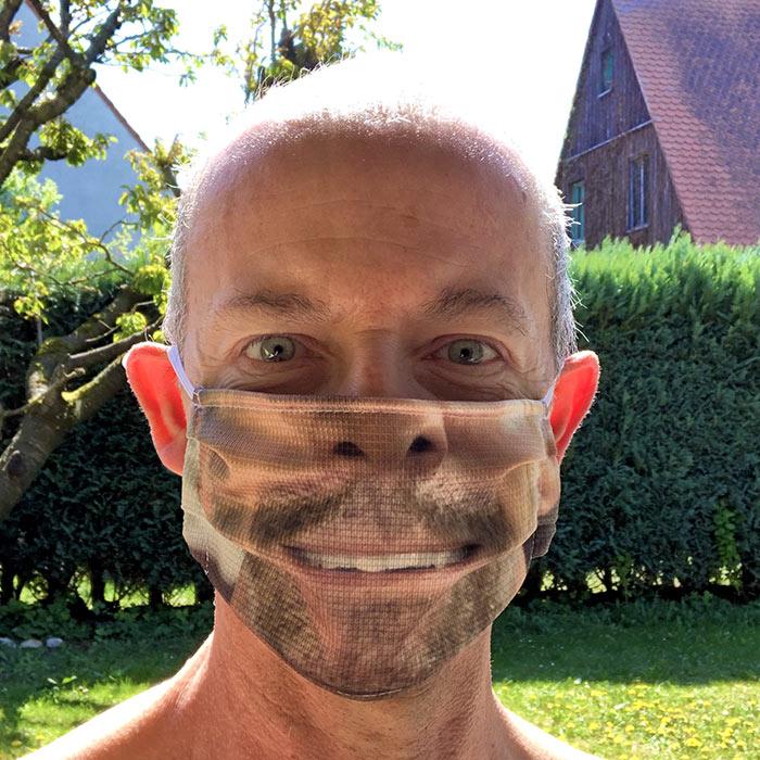Mann mit Maske mit Gesichtsaufdruck