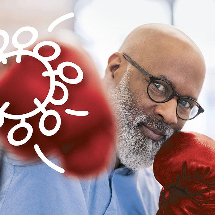 Mann mit roten Boxhandschuhen boxt Virus